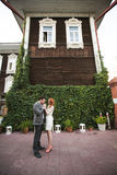 The bride and groom posing near a green fence and old house Stock Image