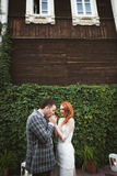 The bride and groom posing near a green fence and old house Royalty Free Stock Images