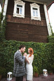 The bride and groom posing near a green fence and old house Stock Images