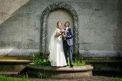 Bride and groom posing at park under floral arch Royalty Free Stock Images