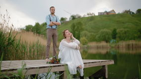 Bride and groom posing on the pier stock video footage