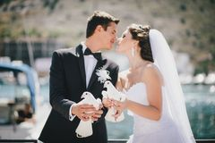 Bride and groom posing with white wedding doves. In a small cove with boats stock photography