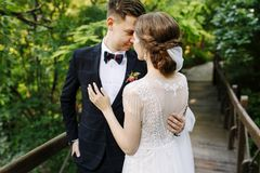 Bride and groom posing on the wooden bridge among greenery. Young people embrace each other and look at each other,happy stock image