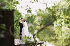 Bride and groom posing on the wooden pier near the pond among greenery. Young people embrace each other, and look at royalty free stock image