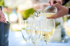 Bride and groom pour into a glass of champagne. At a wedding ceremony Stock Images