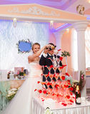 Bride and groom pouring champagne into the glass Stock Image