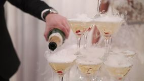 Bride and groom pouring champagne to pyramid of glasses. On party stock video footage