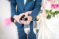 Bride and groom pouring champagne at a wedding ceremony. Bride and groom pouring champagne at a wedding ceremony in hotel Royalty Free Stock Photography