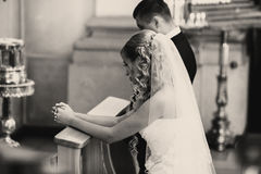 Bride and groom pray standing on the knees during an engagement Royalty Free Stock Photo
