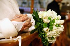 Bride and groom praying in church at wedding ceremony. Royalty Free Stock Image