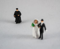 Bride, groom and priest on white. Bride, groom and focused priest on white, wedding concept royalty free stock photos