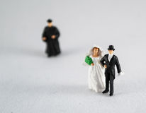 Bride, groom and priest on white. Priest and focused wedding couple, wedding concept royalty free stock image