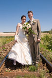 Bride and groom on rails. Bride and groom holding hands and flowers standing in rails with blue sky as background Royalty Free Stock Image