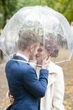 Bride and groom  in the rain while smiling and looking to each other Royalty Free Stock Photography