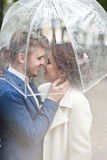 Bride and groom  in the rain while smiling and looking to each other Stock Photos