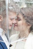 Bride and groom  in the rain while smiling and looking to each other Royalty Free Stock Photo