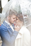 Bride and groom  in the rain while smiling and looking to each other Royalty Free Stock Image