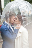 Bride and groom  in the rain while smiling and looking to each other Royalty Free Stock Photos