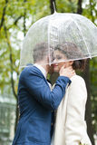 Bride and groom  in the rain while smiling and looking to each other Stock Image