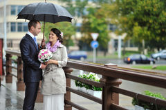 Bride and groom in a rainy weather Stock Image