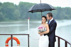 Bride and groom in a rainy weather Royalty Free Stock Image