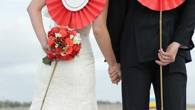 The Bride And Groom Rear View Holding In Their. The bride and groom are standing back and holding in their hands a red paper flowers stock video footage