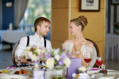 Bride and groom at the reception table Stock Images