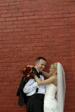 Bride and Groom at red brick wall Stock Photo