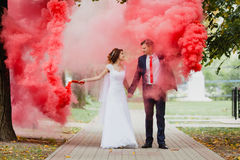 Bride and groom with the red colored smoke Stock Photography