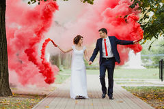 Bride and groom with the red colored smoke Stock Photos