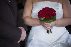 Bride and groom with red roses bouquet Stock Image