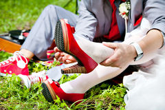 Bride and groom on red shoes. Bride and groom with a bouquet of red shoes and headphones Stock Photos