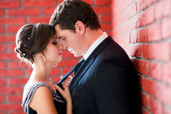 Bride and groom on a red wall background Royalty Free Stock Images