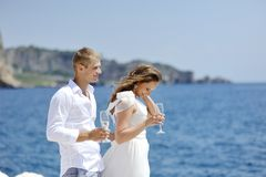 Bride and groom relaxing with champagne glass in wedding day near sea Stock Photography