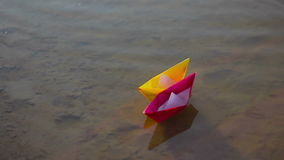 The bride and groom release two color paper ship. The  bride and groom release two color paper ship floating on the water stock video footage