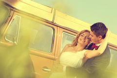 Bride and groom with a retro bus Stock Photo