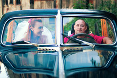 Bride and groom in a retro car Stock Image