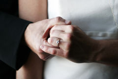Bride and Groom Ring. Groom holding the left hand of his bride displaying her engagement ring, white wedding gress and black suit Stock Image