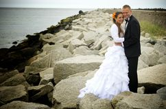 Bride and groom on rocks, Baltic Sea royalty free stock photos