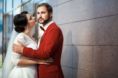Bride and groom, romantic wedding couple in a passionate outburst, near walls of building. Stock Photo
