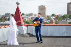 Bride and groom on the roof. Happy gorgeous bride and stylish groom with true emotions on the roof on background of view of city buildings. Groom playing the stock photography