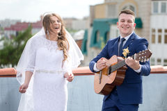 Bride and groom on the roof. Happy gorgeous bride and stylish groom with true emotions on the roof on background of view of city buildings. Groom playing the royalty free stock photo