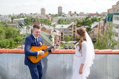 Bride and groom on the roof. Happy gorgeous bride and stylish groom with true emotions on the roof on background of view of city buildings. Groom playing the royalty free stock photos