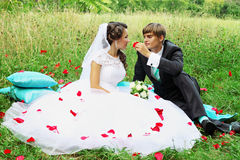 Bride and groom in rose petals Royalty Free Stock Photos