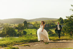 Bride and groom run along the village road enjoying summer weath Stock Image