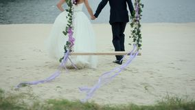 Bride and Groom Run from the Swings to Lake. The bride and groom run from the swings to the lake on the sand stock video