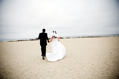 Bride and Groom Running. On the beach after getting married Royalty Free Stock Photo