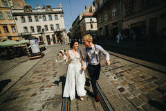 The bride and groom running along streets Stock Photography