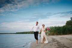 The bride and groom running on the beach, wedding accessories Royalty Free Stock Images