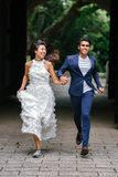 Bride and Groom Running on Concrete Pathway Stock Images